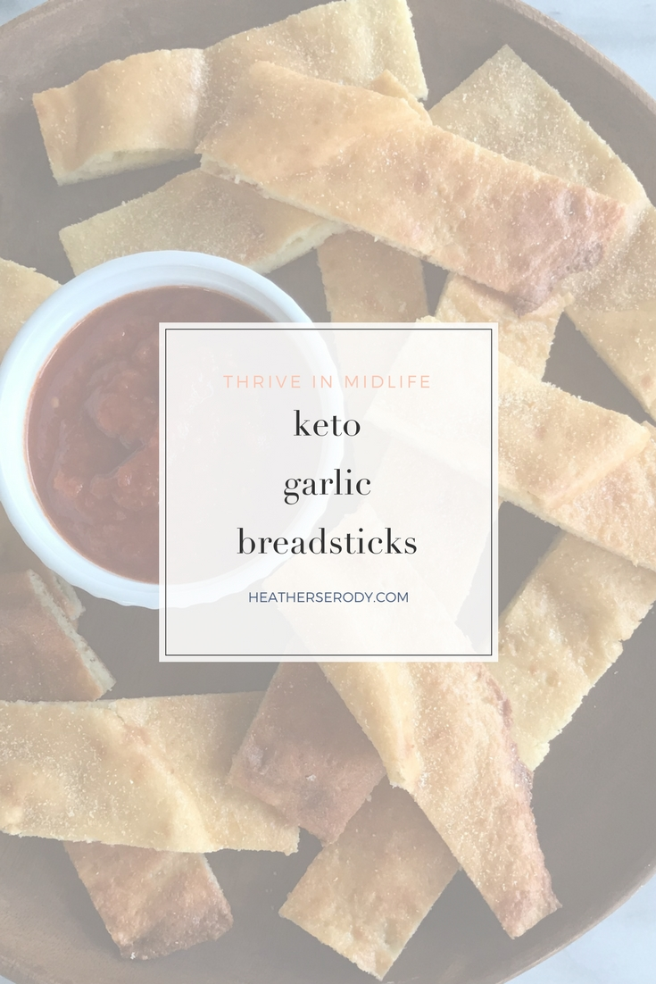 keto garlic breadsticks recipe: Just 3 carbs per 3 breadsticks! This recipe is the result of trying to make my keto bagel dough into keto crackers. The result wasn\'t crackers at all, but delicious breadsticks! I just spread out the dough like a rectangular pizza crust on a parchment-lined baking sheet, & sprinkled it with garlic powder. After it comes out of the oven just let it cool for a few minutes and then cut it into breadsticks with a pizza cutter.  | Thrive In Midlife #keto #ketogen...